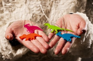 Colourful dinosaur necklaces held in model's hands