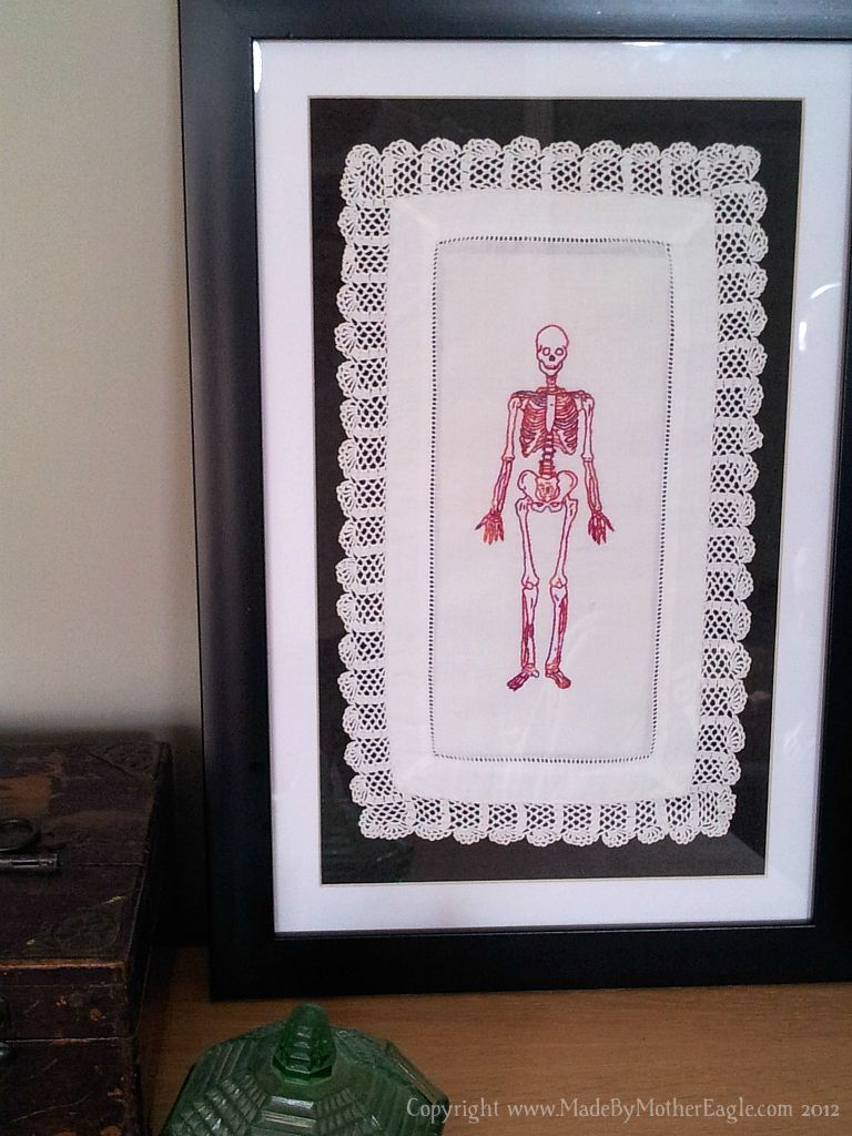 Skeleton embroidered in red onto doily