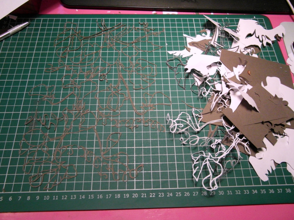 Finished papercut on cutting mat with discarded paper