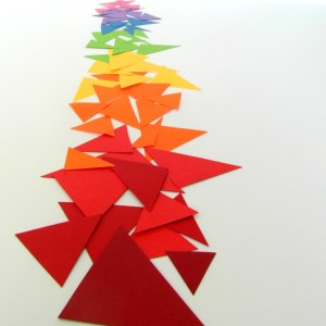 Paper triangles layered along a table in rainbow spectrum