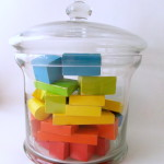 Glass jar filled with wooden blocks layered in rainbow spectrum