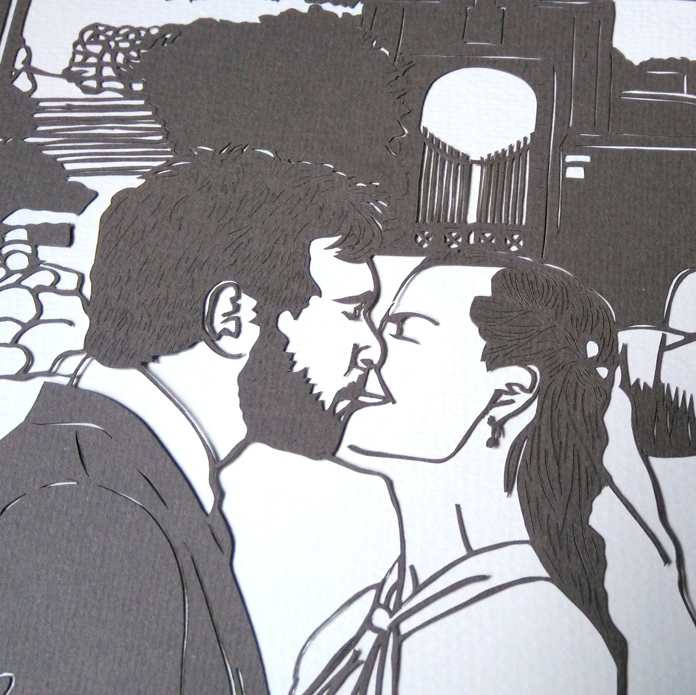 Closeup of papercut showing bride and groom kissing