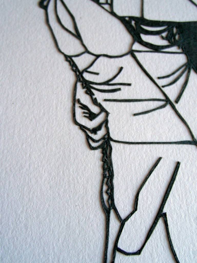 Closeup of papercut detail showing tiny buttons on a wedding dress and the groom's hand