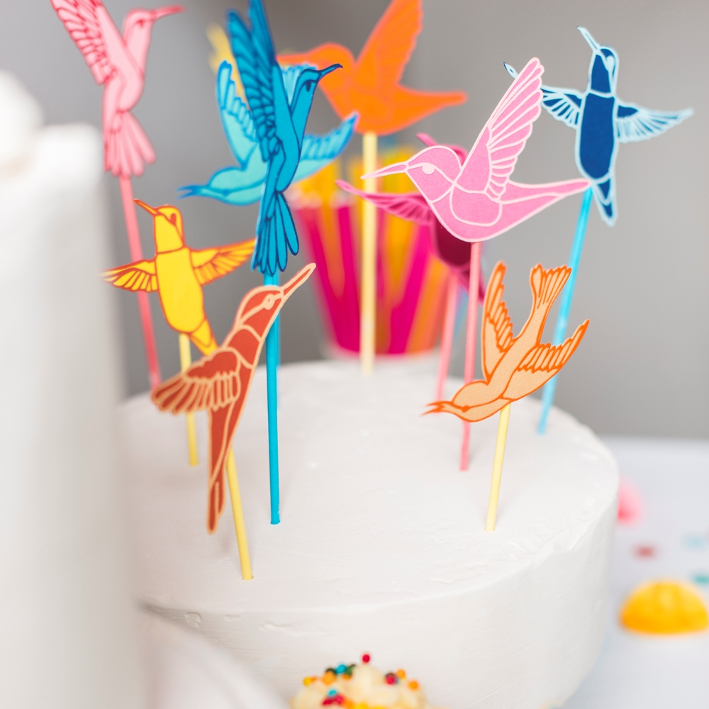 Closeup images showing papercut hummingbird cake toppers in pinks, blues and yellows