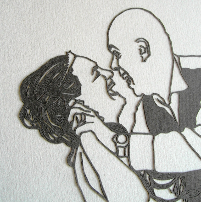 Closeup of papercut image of bride and groom dancing